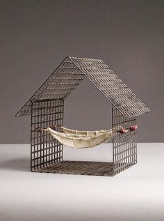 """The Two of Us"""" Metal Sculpture Created by Julie Girardini and Ken Girardini Steel grid house with two boat shapes suspended within. The boats are made from wire and fabric with en caustic coating. This piece is meant to symbolize a couple living side by side in harmony, sharing the safe harbor of a home and the love that dwells within."""