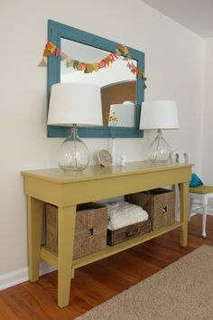 (Entry Way/Living Room) Painted table, clear lamps + big white shades, flowers, storage baskets.