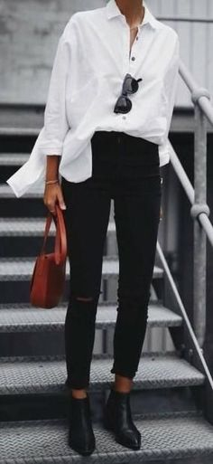 White blouse over black jeans with black boots and red bag.