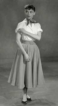 """1952 Audrey Hepburn wearing the """"New Look"""" style of full skirt and white blouse. She makes it her own with her signature black """"flatties"""" ballet slippers. #1950sfashion #audreyhepburn #vintage #skirt"""