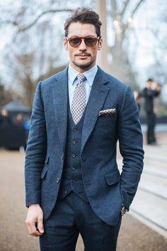 Combo du costumes 3 pièces très réussi grâce à une couleur bleu moucheté tendance, parfaite pour l'hiver. La pochette et la cravate à carreaux gris assortis s'accordent avec l'ensemble et renforcent l'aspect formel. Le côté chic de l'ensemble est à son comble avec les lunettes de soleil et la coupe de cheveux volontairement en bataille. Le côté Sprezzatura n'est jamais très loin. #modehomme #streetstyle #menswear #sprezzatura #chic