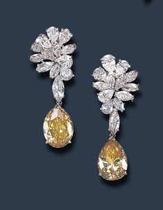 A PAIR OF DIAMOND EAR PENDANTS Each pendant set with a pear-shaped diamond, weighing approximately 9.53 and 10.08 carats, suspended by a marquise-cut diamond from a pear and marquise-cut diamond cluster, mounted in platinum and 14k white gold