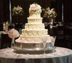Soft pink and white roses accented with maidenhair fern top a fairytale cake.