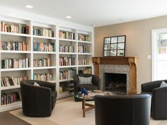 Built-in bookshelves stretch across one wall in this cozy, contemporary living room. Four chairs around the fireplace provide a place for reading or spending time with friends and family.