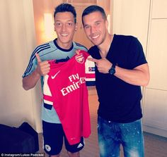 New colours: Ozil (left) showing off his new Arsenal shirt with Gunners striker Lukas Podolski