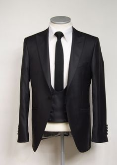 Grooms wedding suit   Black wool & silk mix suit with low cut db scoop waistcoat. This jacket has a lovely cutaway front. made to measure white cotton shirt and knitted silk black tie. £745 3 piece #groom #wedding #suit #bespoke #madetomeasure #black #waistcoat #scoop