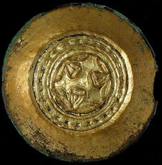 One of a pair of gilded bronze saucer brooches found in a late 5th - 6th century grave during excavations at Market Lavington, Wiltshire.