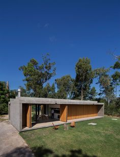 The rectangular house is made primarily of concrete, but its longest external walls are treated differently.