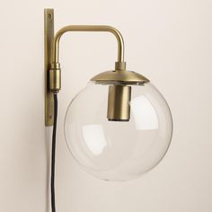 Brighten any corner with our exclusive globe wall sconce, crafted of glass with a dark brass bracket and fixture inspired by mid-century modern style and a plug-in cord for easy installation. Pair two sconces at either end of a bed, sofa, chair or mirror to create decor-enhancing symmetry.