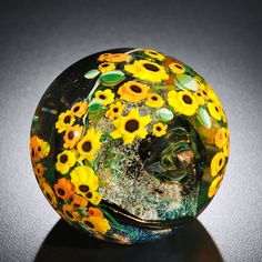 Sunflowers Paperweight by Shawn Messenger. Dichroic glass and bubble inclusions create a glittering backdrop for a bouquet of murrini sunflowers. Hand formed from glass, each paperweight is unique and will vary.