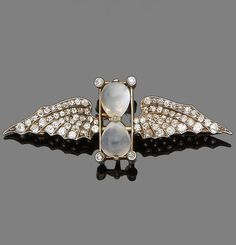 An antique moonstone and diamond brooch, early 20th century. Centrally-set with a moonstone hourglass, highlighted in each corner with old brilliant-cut diamonds, between similarly-cut diamond wings, width 5.8cm. #antique #brooch
