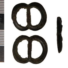 Lead alloy  Buckle. A cast double-looped or spectacle buckle; the frame has lightly bevelled edges on its display face, and is rough on the ...