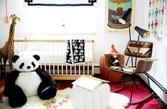 Child-sized stuffed animals surround the light wood crib, white poof, and rocking chair