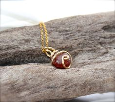 This rough spessartite garnet stone has been wire wrapped in gold tone wire and measures about 3/4 long (including the bail); actual stone is