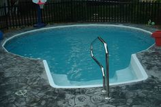 In Ground Pool Featuring A Vinyl Liner Hardscape Fencing Concrete Patio And Deck Jets