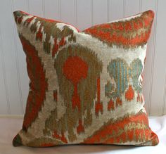 This designer ikat upholstery in terracotta, gold, teal and beige is combined with a chili pepper velvet back. This is a striking pillow that