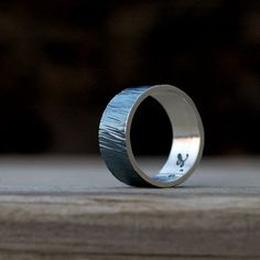 blackened wide wedding band for him. totally unique. totally cool.