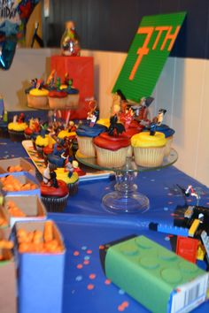 """Lego cupcakes, minifigs from eBay (sniped for about 50 cents each, including shipping).  cereal boxes and juice boxes, wrapped in construction paper and circles cut with 1"""" cutter from amazon (cereal boxes filled with cheetos).  green board from amazon (4.99 add on item) with a 7 made from legos."""