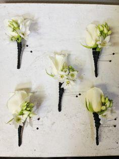 White rose boutonnieres with black ribbon wrap by Seasonal Celebrations. http://www.seasonalcelebrations.com