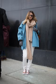 A vibrant blue coat, chunky camel scarf, straight-leg trousers, and rose gold sneakers