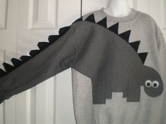 New! Cute Dinosaur Applique with spikey back that trails down his full sleeve spikey tail!!  I design all of my shirts, cut, sew and finish