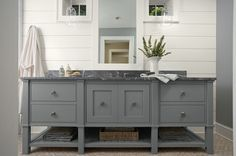 Murphy & Co. Design  Beautiful bathroom with white groove walls, extra-wide gray bathroom vanity with black marble countertop and gray walls.