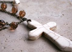 Howlite cross hangs from a brass chain with brown faceted glass beads.