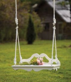 romantic Victorian swing in white with graceful wooden curves with roping and pink roses resting gracefully on the seat