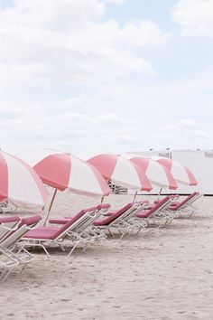 Line up of pink and white beach chairs.