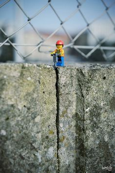 Lego Man with red helmet working with brick by Samsofy   For French photographer Samsofy, Lego is still a great source of inspiration. He has taken an astonishing amount of pictures with LEGO men. In this, he combines the elements of photography, street art, model building and installation to great effect. Forced perspective and well-chosen materials make for some stunning scenes with the plastic yellow people. You can't help but admire the tiny plastic Superman lifting the drain grate.