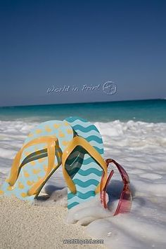 a39e34809c6b78 Take a look at the Two mismatched beach flip-flops with red sunglasses in  the surf on a Caribbean beach prints from WorldInPrint.