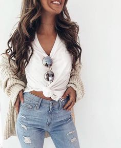 Beige cardigan over white knotted tee with blue jeans.