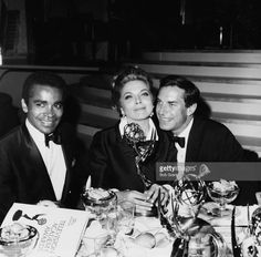 Actors Greg Morris (left) and Martin Landau sitting with actress Barbara Bain as she holds on to her award for the show 'Mission: Impossible', at the Emmy Awards, circa 1968.