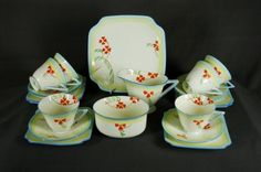 Doulton deco: unnamed tea set incl tea trios, V1309, c1932 (pattern). Stylised branched orange flowers with yellow and blue border and blue highlights and trim.