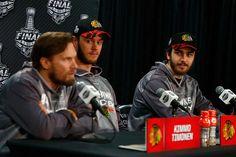 Trevor Van Riemsdyk and Jonathan Toews listen as Kimmo Timonen answers a reporter's question.