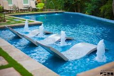 Straight line pool with large tanning ledge and fountains.