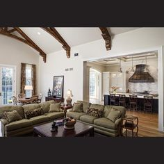 An emphasis on natural materials – stone, metal and wood – is continued in the equally generous, adjacent living room. Here the wood beams, actually hollow and made from existing barn wood, help bring a human scale to the soaring ceilings. Furniture coverings sit within the general palette of earthy tones and were chosen by the interior designer. The placement of the sofa provides a degree of separation between the rooms.