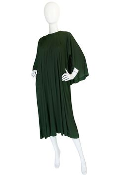 """Exemplifies her use of simple but dramatic cuts and fluid flowing silk-like crepe jersey fabrics. Vertical seams at neckline open to release volume. Unlined; back painted zipper; hidden pockets; signature top-stitching in matching olive thread. Back cape running around shoulders, acts as sleeves, closes w/ hidden snap at back of neck. Dress has thirties feel."" Offered by Shrimpton Couture. ($875 US). https://www.1stdibs.com/fashion/clothing/evening-dresses/"
