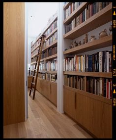 enough bookshelves to need a ladder? be still my heart. also, love using the middle shelf to break up the lines of books with art. and the white behind the shelves.