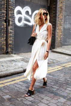 Adenorah pairs a white wrap dress, black mules, and chain link bag for the perfect spring look