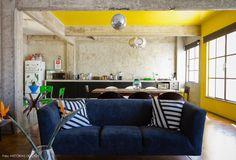 Cozinha integrada com sala de jantar com vigas de concreto aparente e teto pintado de amarelo.
