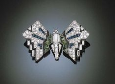 AN ART DECO BUTTERFLY BROOCH   The pavé-set diamond wings, interspersed with buff-top calibré-cut sapphires and demantoid garnets, accented by black enamel to the baguette and bullet-cut diamond body, mounted in platinum (one small demantoid garnet deficient), circa 1925