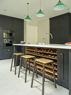 Charcoal grey black shaker style kitchen with a bespoke oak wine rack built into one side of the kitchen island. Green glass pendant island lighting and breakfast bar with vintage science lab stools.