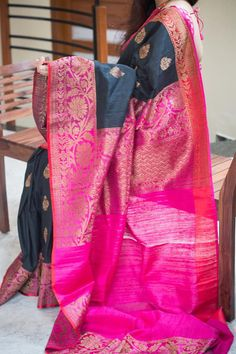 A gorgeous Black Pure banaras silk saree with pink coloured double sided zari border and rich pink zari pallu. Rich golden zari pallu with attached blouse.