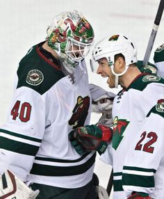 Minnesota Wild goalie Devan Dubnyk (40) and teammate Jason Pominville (29) celebrate the team's 4-0 win over the Edmonton Oilers in an NHL hockey game Friday, Feb. 20, 2015, in Edmonton, Alberta. (AP Photo/The Canadian Press, Jason Franson)