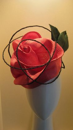 Wild rambling rose. Hand dyed straw freeform scuptured into a rose with green tulle covered wire wrapping like a vine. Two leather leaves at the back.