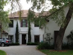 This dark red brick Florida home was painted white to blend into this waterfront, Tuscan style neighborhood.
