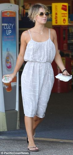 Shady lady: The Big Bang Theory star wore large yellow sunglasses and looked pretty in a grey and white dress