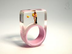 Warm-hearted – romantic lovers ring with kissing mini figures and a butterfly on a pink ring made of resin  ///// © Isabell Kiefhaber www.geschmeideunterteck.de