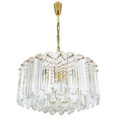 """Stunning three-tier crystal and gilded brass Kalmar chandelier in excellent condition. Measuring approximately 20 inches in diameter this chandelier holds up to 13 bulbs (12x e14 with 40W max and 1x e27 with 100W max) and illuminates beautifully. Overall heights is 32"""" at the moment. It has been professionally cleaned and rewired. Please note that we can provide you with different sizes and length of stems or even switch to a chain, according to your requirements. Hollywood Regency, 1975."""